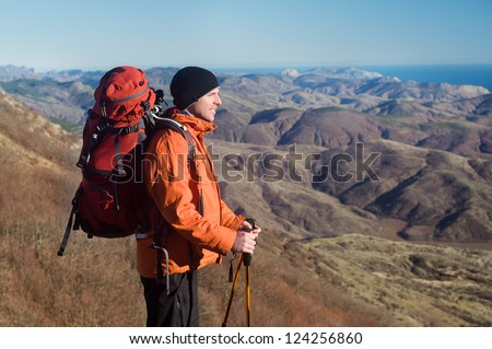 Hiking man with backpack and hiking poles looking at beautiful scenery, view of the Crimean mountains, Ukraine