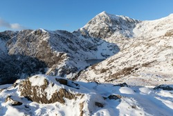 Hiking on Pyg Track climbing Mount Snowdon, snowcaped Snowdonia, North Wales in the sun and snow
