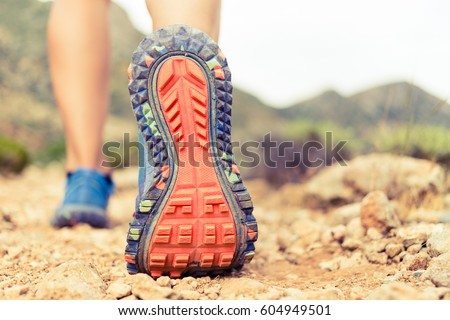 Hiking or running woman in beautiful mountains inspirational landscape. Sole of sports shoe and legs on rock trail. Hiker trekking or walking of footpath. Healthy fitness lifestyle outdoors.