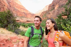 Hiking people - hiker couple on hike outdoors enjoying active lifestyle in beautiful mountain landscape in Zion National Park. Multiracial Asian woman and Caucasian man in Utah, USA.