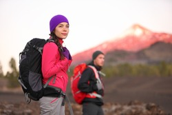 Hiking people on mountain. Hiker couple walking with backpack in high altitude mountains. Young woman hiker in focus trekking at sunset Tenerife, Canary Islands, Spain.