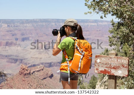 Hiking photographer taking pictures in Grand Canyon at hike by south rim by Bright Angle trail. Young woman hiker enjoying nature landscape in Grand Canyon, Arizona, USA.