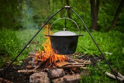 Hiking pot, Bowler in the bonfire. Fish soup boils in cauldron at the stake. Traveling, tourism, picnic cooking, cooking at the stake in a cauldron, fire and smoke.
