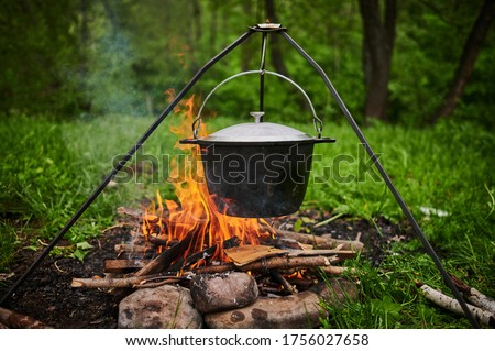 Hiking pot, Bowler in the bonfire. Fish soup boils in cauldron at the stake. Traveling, tourism, picnic cooking, cooking at the stake in a cauldron, fire and smoke. Stock photo ©