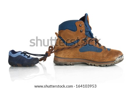 Hiking shoes from father and son are bund together - symbol of love and connection - stock photo