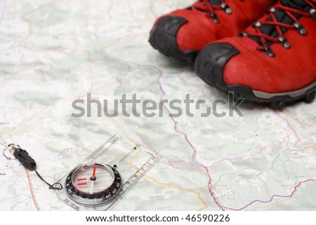 Hiking shoes on map and compass