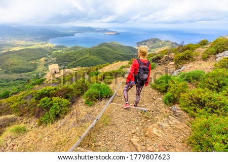 Hiking to Volterraio Castle. Backpacker woman looking views of Portoferraio Gulf, Elba Island. Stone stairs along Monte Volterraio with medieval fortress dominates.Tourism in Tuscany Italy destination Foto stock ©