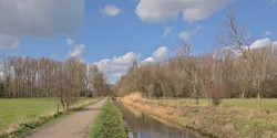 Hiking trail along a draining canal in the Flemish countryside near Schoonaarde, Belgium