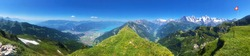 hiking trail panorama in the swiss mountains alps in summer / spring. Panoramic view at the summit of the mountain with the swiss national flag