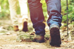 Hiking trail path in action on a mountains or forest with hiking shoes. male and female hikers shoes. are walking through forest path wearing mountain boots and walking sticks. Destination Experience