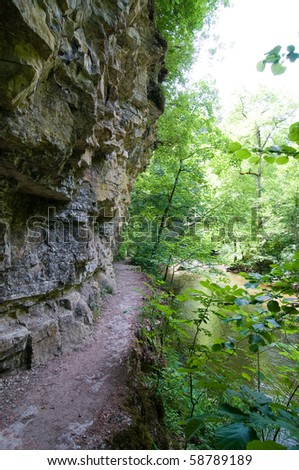 hiking trail under a craning cliff alongside a river