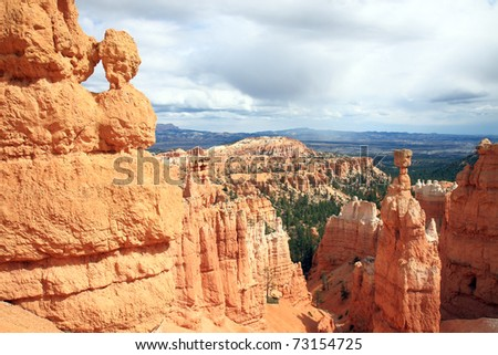 Hiking trails wind through dramatic landscape at Bryce Canyon National park is decorated with orange sandstone pinnacles, towering over canyon floor, with unique shapes carved by nature's forces