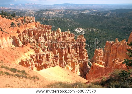 Hiking trails wind through luminous orange sandstone spires, sculpted by wind and water erosion, towering above Bryce canyon's valley floor