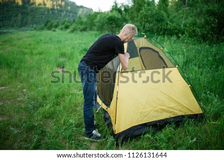 hiking, traveling, hiking, trekking and people concept - smiling friends, setting up a tent outdoors. to collect a tent in nature.
