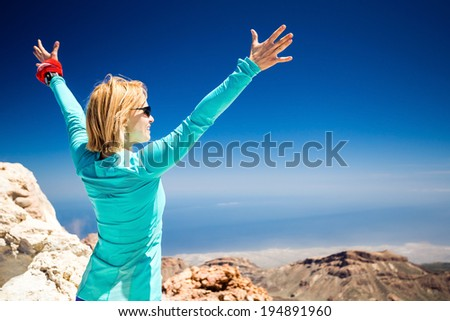 Hiking woman and success in mountains motivation inspiration. Accomplish Fitness and fhealthy lifestyle outdoors. Trail runner beautiful with arms outstretched on island, sea ocean in background.