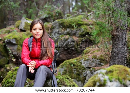 Hiking. Woman hiker in forest taking a rest sitting down. Beautiful young Asian Caucasian model. From La Caldera, Aguamansa, Orotava, Tenerife, Canary Islands, Spain. Winter.