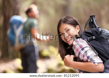 Hiking. Woman hiker smiling in forest with male hiker in the background. Mixed-race Asian Caucasian female model happy. From Aguamansa, Tenerife, Spain