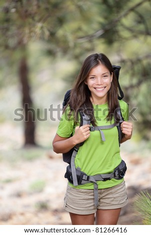 Hiking. Woman hiker smiling standing outside in forest with backpack. Outdoors portrait of happy beautiful young asian woman model