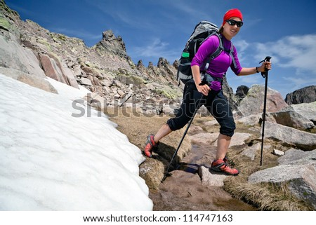 Hiking woman in rocky mountains with snow. Trekking with backpack in sunny Corsica, France.