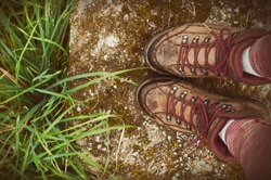 Hiking.Woman legs with hiking boots on the mountain path, top view. Stones and green grass