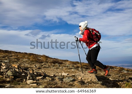 Hiking woman over blue sky, Nordic Walking in Autumn mountains