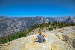 Hiking woman relaxing sitting at Sentinel Dome summit of Yosemite National Park. Happy after hiking and enjoying El Capitan view at Sentinel Dome. Summer travel holidays in California, United States.