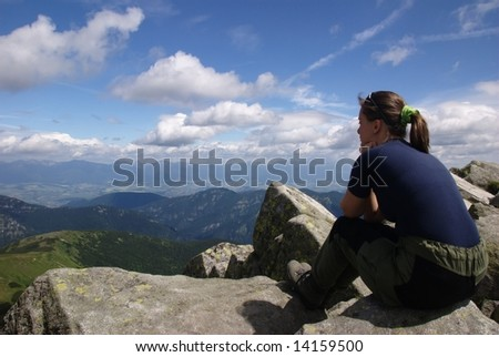Hiking woman siting on rocks looks at beautiful  mountains and blue sky