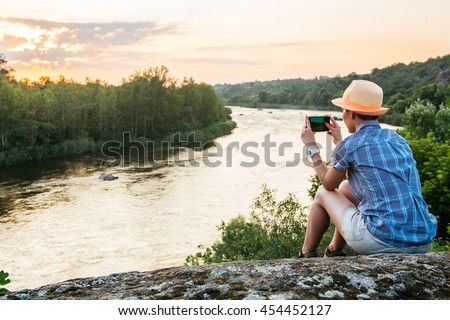 Hiking woman use smart phone making photo of beautiful river nature landscape. Traveler girl sitting on cliff edge, taking picture on mobile phone. Tourist with camera in mountains outdoor on sunset.