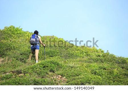 hiking young asian woman hiker climbing to mountain peak