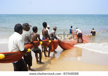 HIKKADUWA, SRI LANKA - FEB 19: Local fishermen pull net from the ocean on February 19, 2011 in Hikkaduwa, Sri Lanka. Fishing in Sri Lanka is a tough job but this is the way they earn their living