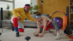 Hilarious fat afro-american instructor training weak unfit bearded man lifting up cookies plate like dumbbells. Fake fitness. Parody. Concept of fun, entertainment.