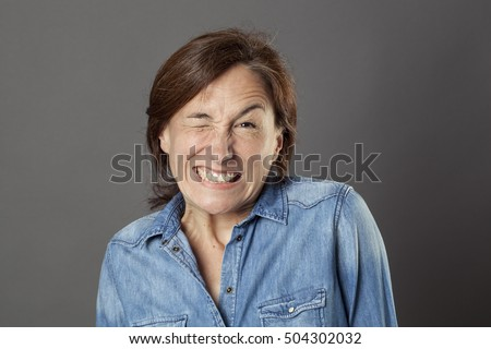 hilarious middle aged woman showing her teeth in trying to wink for fun dynamic flirting, humorous portrait over grey background