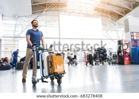 Hilarious smiling man carrying luggage