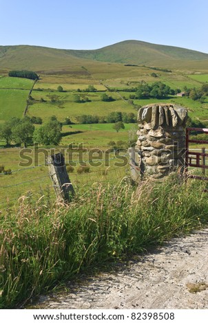 Hill farming in the Sperrin mountains, Co Londonderry, Northern Ireland. A pillar built from local rock makes a typical gate post and sheep graze in little stone walled fields on a sunny summer day.