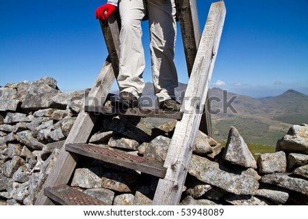 Hill walker climbing a ladder over a stone wall on a sunny day in Snowdonia with Snowden in the background