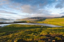 Hills covered with green grass and lakes in West Iceland on a cloudy day
