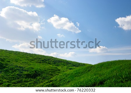 Hills covered with green grass under blue sky Summer landscape background
