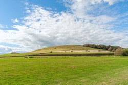 Hills with a green lush grass,fields and meadows against blue cloudy sky.