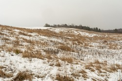 Hills with dry grass are covered with snow. Gloomy winter day. Nature landscape background