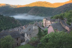 Hillside view of the quaint and charming medieval French village of Conques, Aveyron, a popular summer tourist destination in the Occitanie region of France.