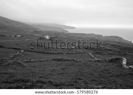 Hilly landscape with stone walls and a lonely house and with a view looking out into the sea in black and white. #579580276