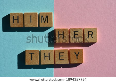 Him, Her, They, gender pronouns, words in wooden alphabet letters on pink and blue background Stock photo ©