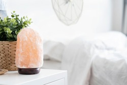 Himalayan pink salt crystals lamp on the table in bedroom, therapy healthy.