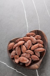 Himalayan pink salt roasted almonds in a wooden bowl on a marble table