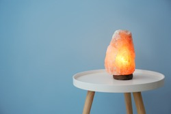 Himalayan salt lamp on table against color background