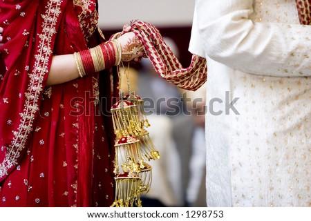 hindu bride walks behind husband holding garb