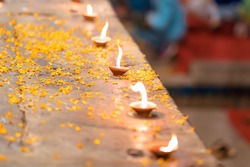 Hindu Diwali festival. Burning candles standing in a row on a table sprinkled with flower petals. Top view, close-up