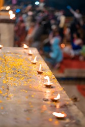 Hindu Diwali festival. Burning candles standing in a row on a table sprinkled with flower petals. Blurred background. Top view, close-up.