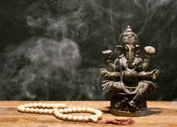 Hindu god Ganesh on black background. Statue and rosary on wooden table with a smoke of incense. Copy space.