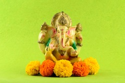 Hindu God Ganesha. Ganesha Idol on Green Background with flowers.